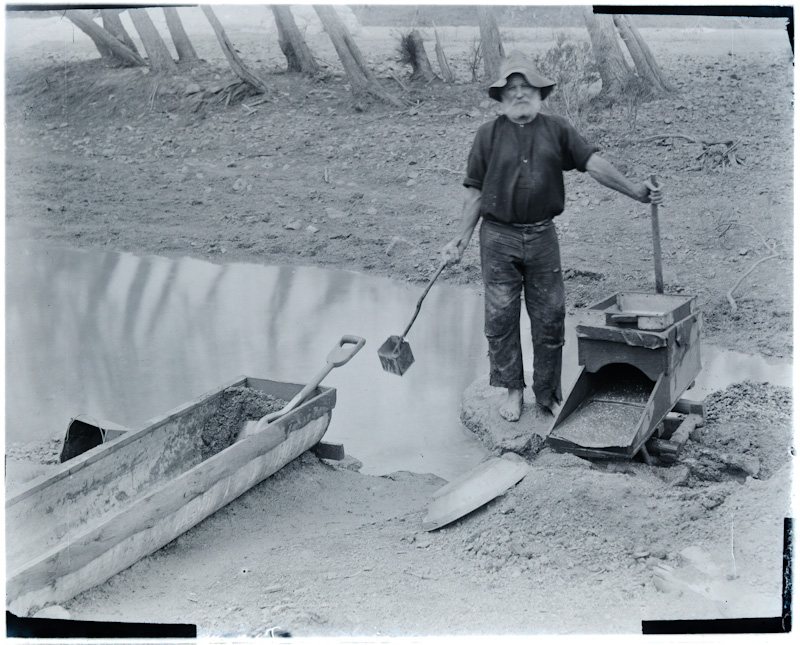 Miner with equipment for alluvial gold mining, Copperfield River